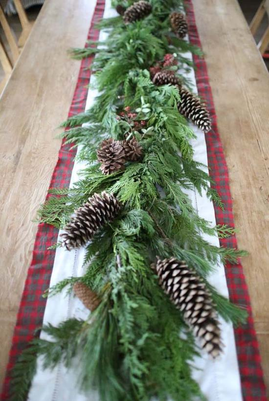 A Rustic Holiday Table Runner Out Of Pinecones Greenery And Plaid Fabric We Love The Natural Look But You Could Add In Few Colorful