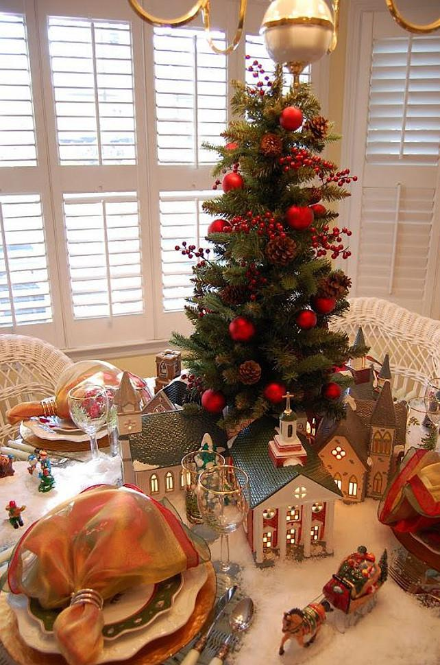 heres a festive christmas tablescape featuring a winter village houses with snowy scene and a beautiful miniature christmas tree the tree is decorated