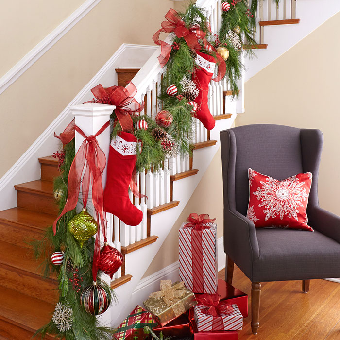 the staircase is one of the best places for displaying the family stockings and add a garland to make it a focal point the oversized ornaments are taking