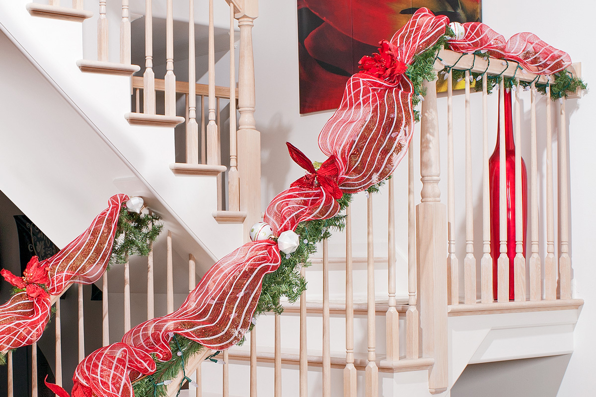 heres an adorable way to decorate your stairways a candy cane printed tutu is wrapped neatly on the railings along with the green garland