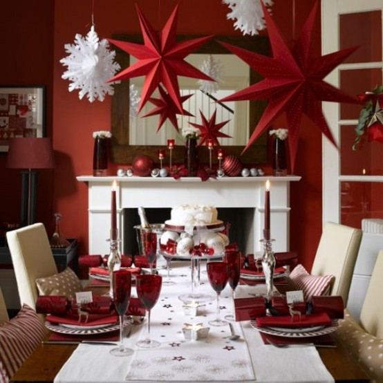 the red christmas decorations in this dining room is simply mesmerizing the red stars christmas balls and candle holders complement well with the white