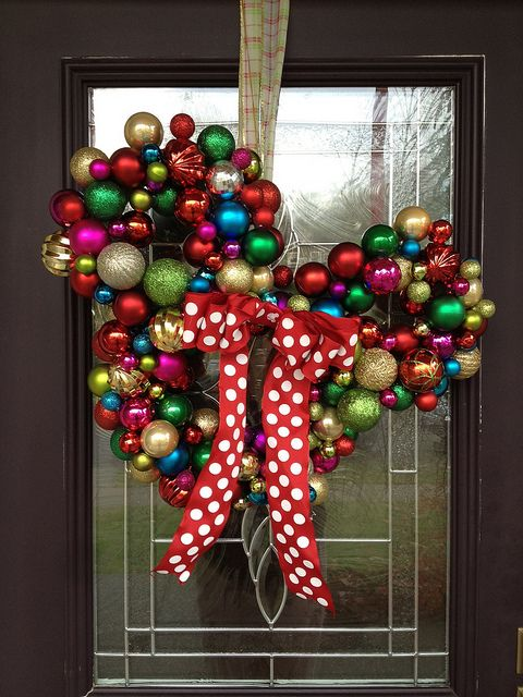 this mickey mouse door wreath will complement your christmas theme very well made with ornaments and baubles this wreath will let your guests know that