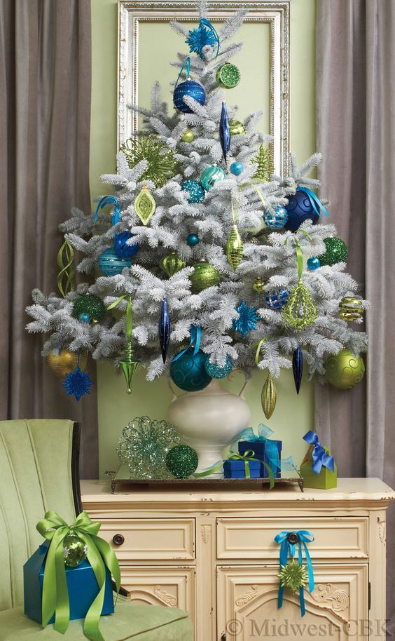 the teal and green trims in a white tree can glamorize even the drabbest of interiors this teal christmas decoration idea gets a double thumbs up from our - Teal Green Christmas Decorations