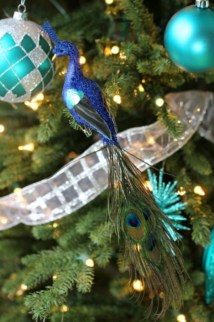 while we can see plenty of teal ornaments hanging on this christmas tree the peacock ornament clearly takes the cake look how beautifully it is perched on