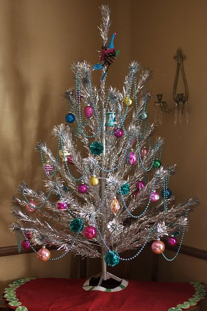 heres a beautiful vintage aluminum christmas tree in all its finery the ornaments especially the garlands are making it look as if its been teleported