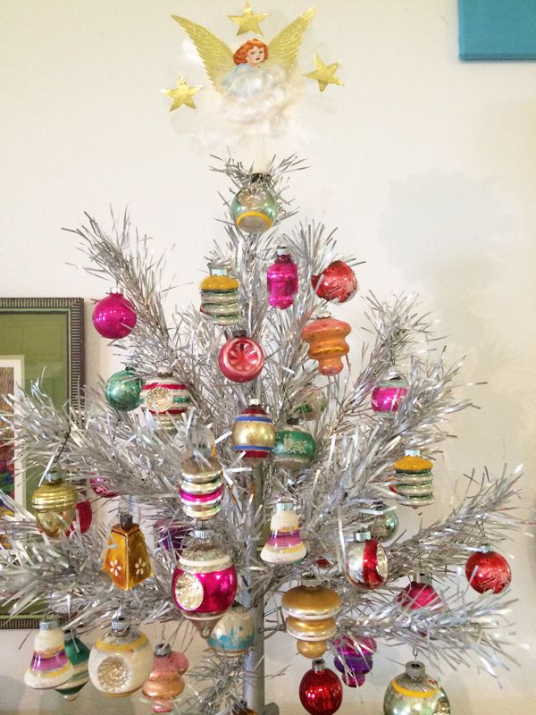 a sparkly aluminum christmas tree is decorated with kitsch ornaments we rarely get to see such beautiful ornaments on display and the tree topper is also - Vintage Silver Christmas Tree