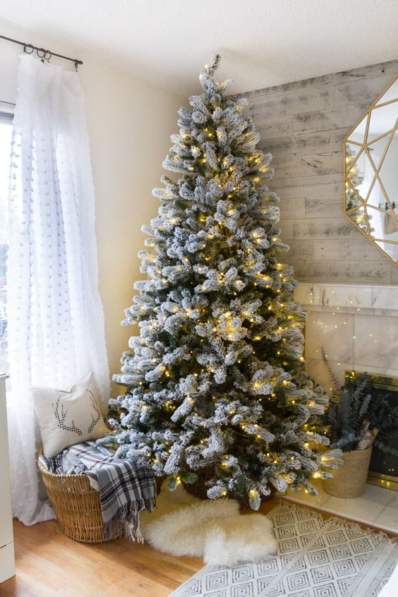 people who want to lend a natural look to their decoration can go for this simple flocked christmas tree decorated only with lights - Decorated Flocked Christmas Trees