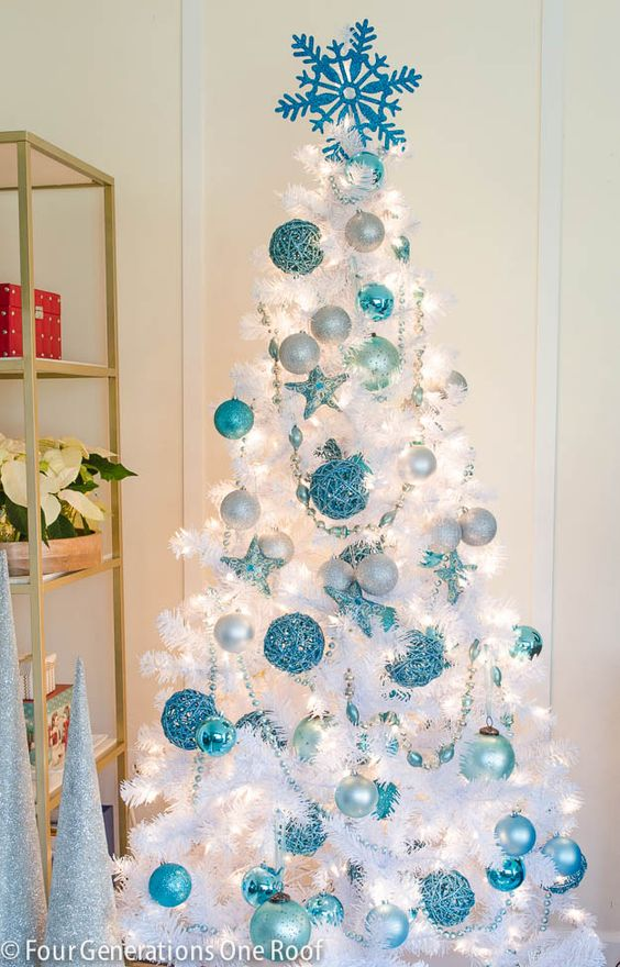 this white christmas tree is decorated with beautiful blue ornaments in different patterns
