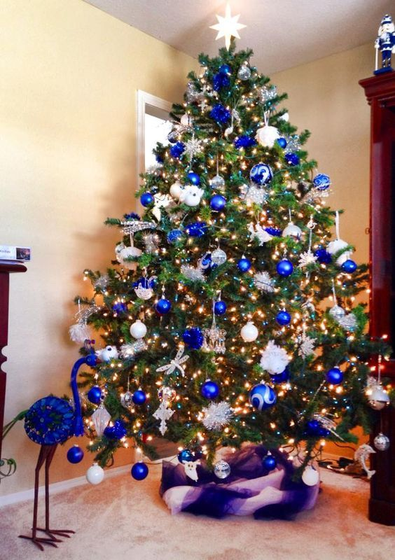 this large sized christmas tree is decorated with wonderful blue and white ornaments in varying sizes we can even see a dragonfly ornament - White And Blue Christmas Tree