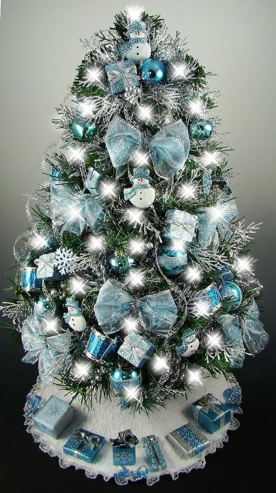 this blue tabletop christmas is decorated with all sorts of fun and quirky ornaments like bows snowflakes snowmen drums baubles and gift boxes - Turquoise Christmas Tree Decorations