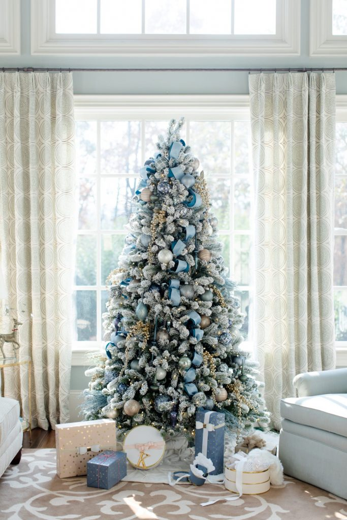 a beautifully flocked christmas tree is decorated with icy blue ornaments and ribbons a few other shades are also incorporated in this dcor like silver - Silver And Gold Christmas Tree Decorations