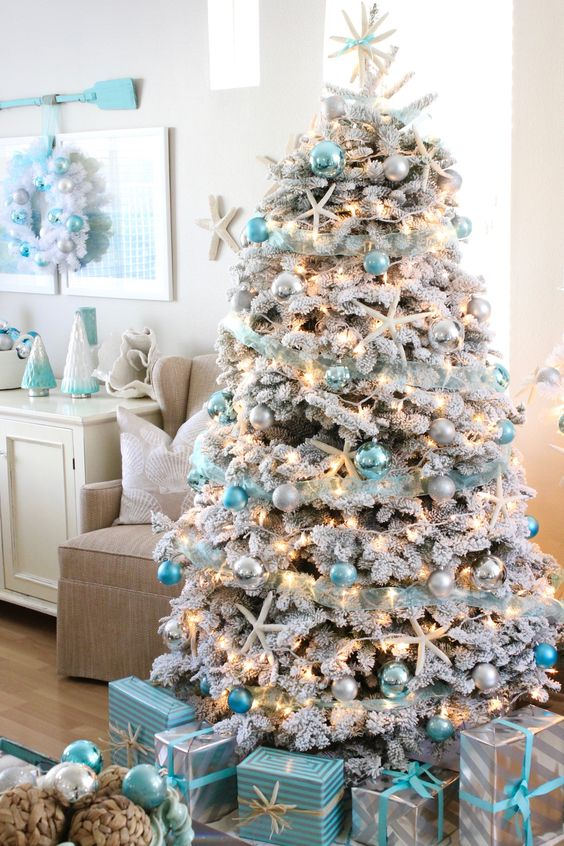 this flocked coastal themed christmas tree is decorated with pretty turquoise ornaments in light and dark shades apart from the baubles clay starfish