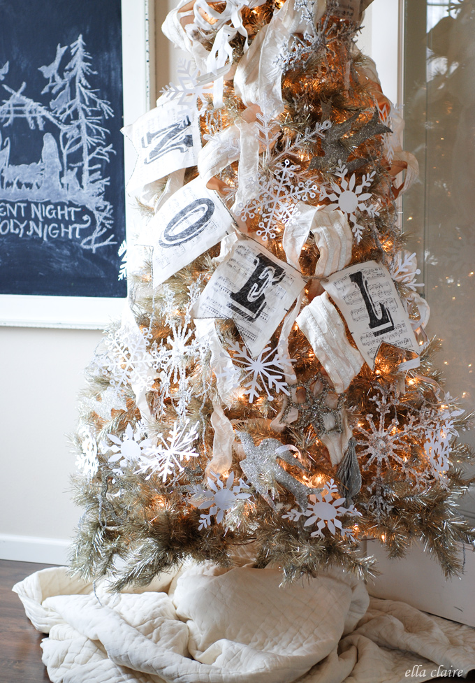 a simple beige ribbon is used to decorate this small sized christmas tree apart from that buntings crystal ropes flags and tulle are used to decorate