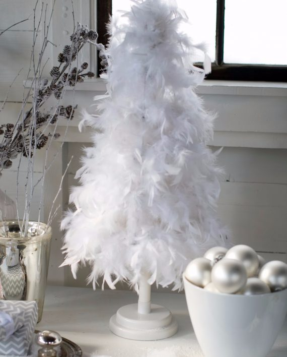 a stark white tabletop feather christmas tree is placed on a shelf along with a bowl of ornaments and a vase with pinecone branches - Feather Christmas Tree Decorations