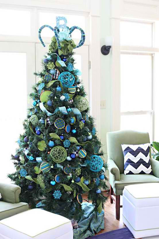 Have this wonderful Christmas tree by decorating it with green ribbons, blue ornaments and blue snowflakes. Yarn balls and diy wooden ornaments would do ...