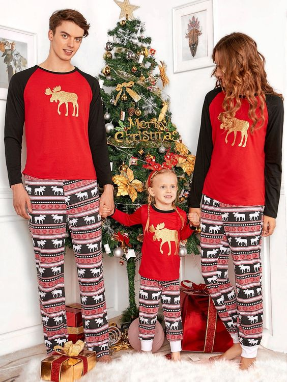 this picture features a family wearing red and black sweater with mule printed in gold on it theyve paired the sweaters with printed pajamas in festive - Black Family Christmas Pictures