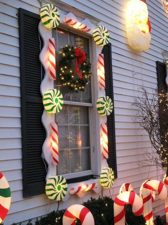 this ones indeed looking very adorable as the house is decorated with lighted candy canes and peppermint candies its making the house look like a candy - Candy Cane Outdoor Christmas Decorations