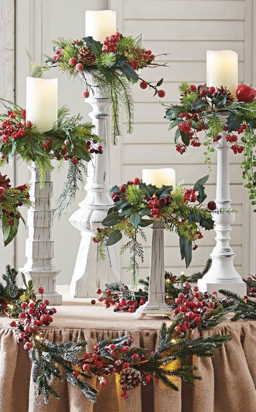 decorate the burlap covered table with decorative vines sprigs of evergreen holly leaves hypericum berry and pedestal candle holders