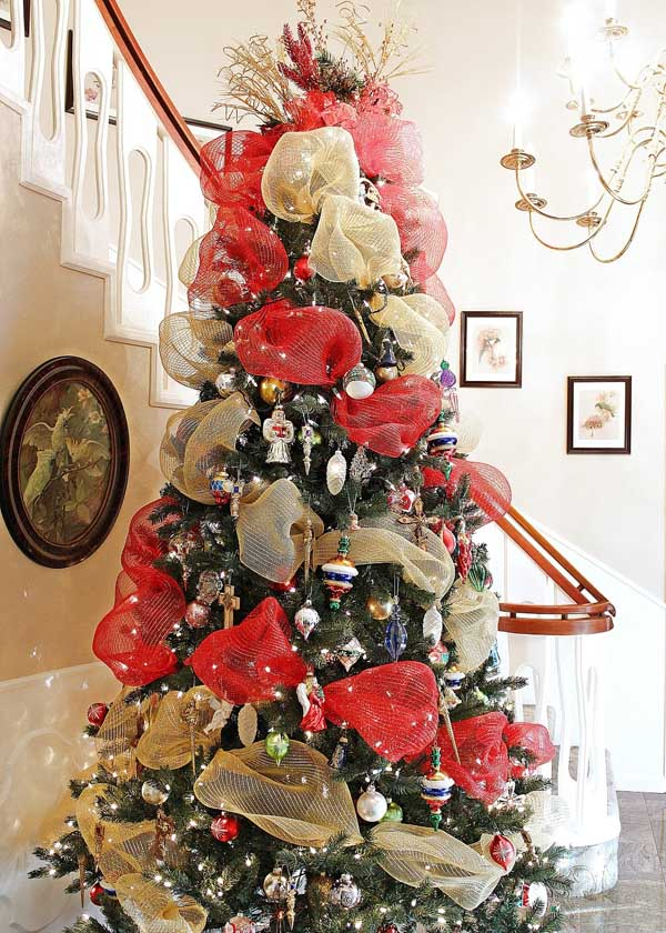 this traditional christmas tree is brought to life with the bright red and cream ribbons contrasted with christmas decorations