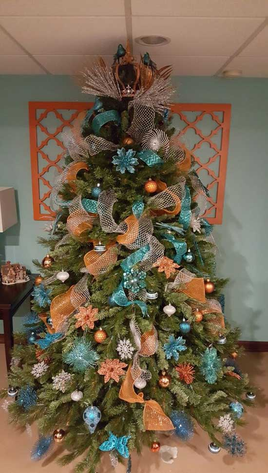 an interesting color combination of orange and blue flowers makes this a distinctive christmas tree