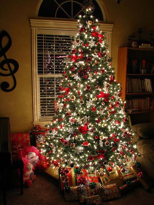 this tree couldnt be more christmassy with jolly red decorations and white christmas lights if you home has subtle interiors youll love the depth and